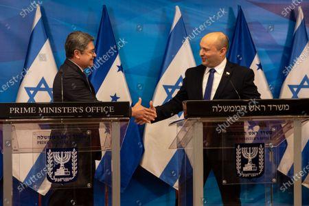 Israeli Prime Minister Naftali Bennett (R) and  Honduran President Juan Orlando Hernandez (L) shake hands after making statements during a press conference at the Prime Minister's Office in Jerusalem, Israel, 24 June 2021.