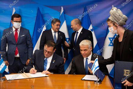 Israeli Prime Minister Naftali Bennett (R-back) talks with Honduran President Juan Orlando Hernandez (L-back) as Israeli Foreign Minister Yair Lapid (2-R) and Honduran Foreign Minister Lisandro Rosales Banegas (2-L) sign agreements between their two countries at the Israeli Prime Minister's Office in Jerusalem, Israel, 24 June 2021.