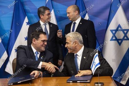 Israeli Prime Minister Naftali Bennett (R, rear)) and Honduran President Juan Orlando Hernandez talk as Israeli Foreign Minister Yair Lapid (R, front) and Honduran Foreign Minister Lisandro shake hands after signing agreements at the Prime Minister's Office  in Jerusalem, Israel, on Thursday, June 24, 2021.