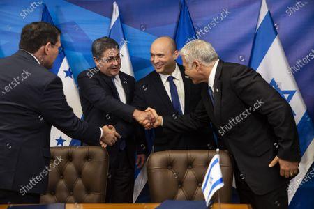 Israeli Prime Minister Naftali Bennett (C), Honduran President Juan Orlando Hernandez (2nd L), Israeli Foreign Minister Yair Lapid (R) and Honduran Foreign Minister Lisandro (L) shake hands after signing agreements at the Prime Minister's Office  in Jerusalem, Israel, on Thursday, June 24, 2021.