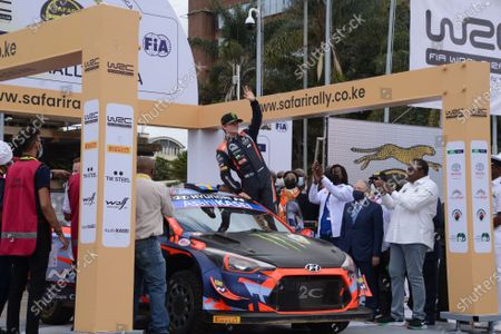 Norway driver Oliver Solberg waves to the crowd from his car as Kenya's President Uhuru Kenyatta and FIA (Fédération Internationale de l'Automobile) president Jean Todt looks on during the official flag off ceremony of the 2021 World Rally Championship (WRC) safari rally at KICC grounds in Nairobi. The safari rally makes a comeback following a 19 years hiatus.