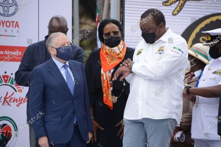 Kenya's president Uhuru Kenyatta looks at his watch in the company of FIA (Fédération Internationale de l'Automobile), president Jean Todt and minister for sports Amina Mohammed during the official flag off ceremony of the 2021 World Rally Championship (WRC) safari rally at KICC grounds in Nairobi. The safari rally makes a comeback following a 19 years hiatus.