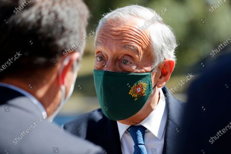 Portuguese President Marcelo Rebelo de Sousa wears a face mask with the presidency coat of arms during a visit to an inoculation center operated by the Portuguese armed forces at Lisbon University's sports stadium, . The Lisbon region's recent surge in COVID-19 cases is powering ahead, with new infections pushing Portugal's number of daily cases to a four-month high, as a report by health experts found fault with the government's pandemic response