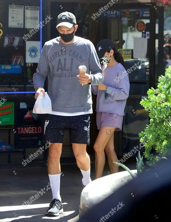 Stock Image of Exclusive - Ashton Kutcher and Mila Kunis were spotted out in Sherman Oaks, as they took their 2 Kids for Ice Cream. The family masked up, despite the lift on masks in LA, as they stepped out of their Tesla SUV. They looked like a normal family as they enjoyed the sweet treats together. Ashton couldn't wait to get a taste of his Ice Cream Cone one he was safely back in the car
