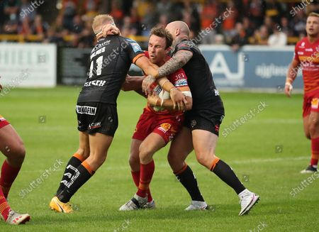 Catalans Dragons' James Maloney in action with Castleford Tigers' Oliver Holmes and Nathan Massey