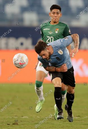 Uruguay's Nahitan Nandez, front, fights for the ball with Bolivia's Ramiro Vaca during a Copa America soccer match at Arena Pantanal in Cuiaba, Brazil