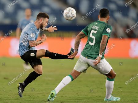 Uruguay's Nahitan Nandez, left, fights for the ball with Bolivia's Adrian Jusino during a Copa America soccer match at Arena Pantanal in Cuiaba, Brazil