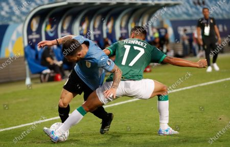 Uruguay's Nahitan Nandez, left, fights for the ball with Bolivia's Roberto Fernandez during a Copa America soccer match at Arena Pantanal in Cuiaba, Brazil