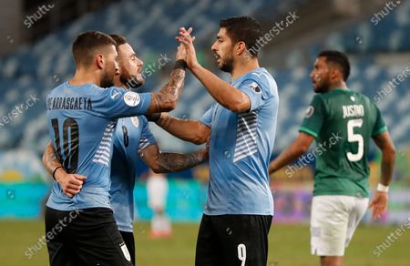 Uruguay's Luis Suarez, right, celebrates with his teammates Giorgian de Arrascaeta (10) and Nahitan Nandez (8) after Bolivia's goalkeeper Carlos Lampe scored an own goal during a Copa America soccer match at Arena Pantanal in Cuiaba, Brazil