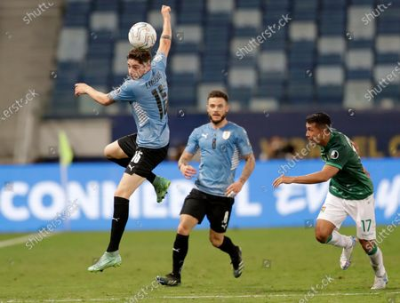 Uruguay's Camilo Candido, left, heads the ball as teammate Nahitan Nandez and Bolivia's Roberto Fernandez look on during a Copa America soccer match at Arena Pantanal in Cuiaba, Brazil