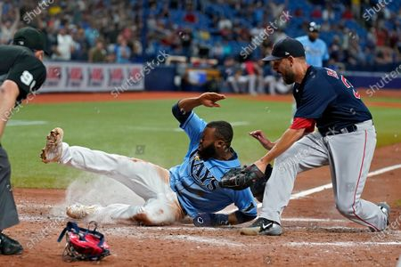 Tampa Bay Rays' Manuel Margot scores ahead of the tag by Boston Red Sox relief pitcher Matt Barnes on a wild pitch by Barnes during the ninth inning of a baseball game, in St. Petersburg, Fla