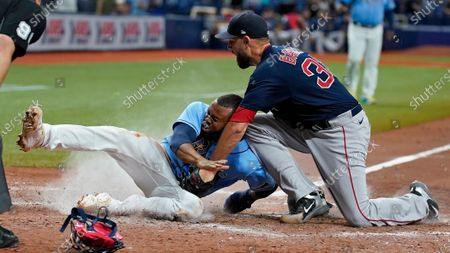 Tampa Bay Rays' Manuel Margot, left, scores ahead of the tag by Boston Red Sox relief pitcher Matt Barnes on a wild pitch by Barnes during the ninth inning of a baseball game, in St. Petersburg, Fla