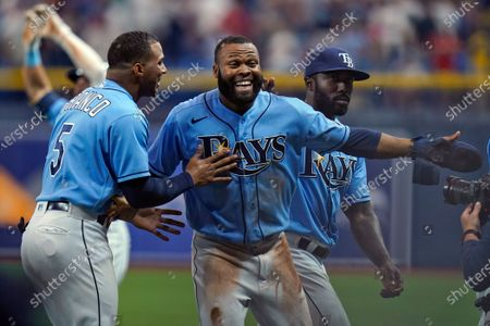 Tampa Bay Rays' Manuel Margot, center, celebrates with teammates, including Wander Franco, left, after scoring on a wild pitch by Boston Red Sox relief pitcher Matt Barnes during the ninth inning of a baseball game, in St. Petersburg, Fla