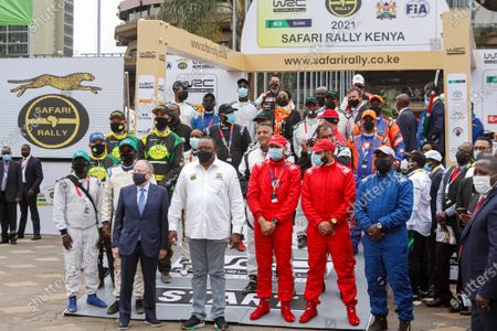 Kenya's President Uhuru Kenyatta (C) and FIA (Fédération Internationale de l'Automobile) president Jean Todt (L) pose for a photo with some of the rally drivers during the official flag off ceremony of the 2021 World Rally Championship (WRC) safari rally at KICC grounds. President Uhuru Kenyatta flagged off the 2021 World Rally Championship (WRC) Safari Rally at the Kenyatta International Convention Center in Nairobi, Kenya. Kenya Safari Rally makes a comeback after 19years and this year the Championship has attracted 58 entrants from across the world.  After the flag off from the KICC, the cars headed to Kasarani for a spectator race to showcase their skills to the public. On Friday June 25, 2021 the main race will kick off from the main Service Park at the KWS Training Institute in Naivasha along the Nairobi-Nakuru highway in Kenya.