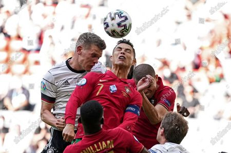 Germany's Matthias Ginter, left, and Portugal's Cristiano Ronaldo challenge for the ball during the Euro 2020 soccer championship group F match between Portugal and Germany in Munich