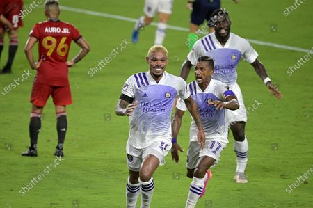Orlando City midfielder Junior Urso (11), front, celebrates after scoring a goal as forward Nani and forward Daryl Dike, right, come to congratulate him during the second half of an MLS soccer match against Toronto FC, in Orlando, Fla