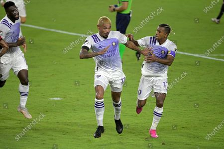 Orlando City midfielder Junior Urso (11), center, celebrates after scoring a goal as forward Nani and forward Daryl Dike, left, come to congratulate him during the second half of an MLS soccer match against Toronto FC, in Orlando, Fla