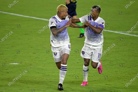 Orlando City midfielder Junior Urso (11), left, celebrates after scoring a goal as forward Nani comes to congratulate him during the second half of an MLS soccer match against Toronto FC, in Orlando, Fla