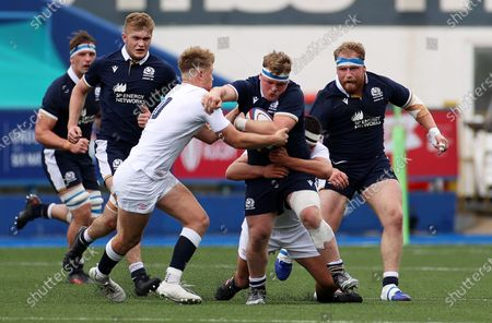 Patrick Harrison of Scotland is tackled by Fin Smith and Lucas Brooke of England.