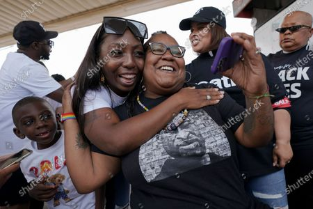 """Jennifer Starr Dodd, right, is embraced by Nikki Johnson as her son, 6-year-old Brandon Johnson looks, after a sentence of 22 1/2 years is announced for former Minneapolis police officer Derek Chauvin in the murder of George Floyd, at George Floyd Square where Floyd was killed, in Minneapolis. Judge Peter Cahill told Floyd's family members that """"I acknowledge and hear the pain that you're feeling,"""" before sentencing Chauvin to 22 1/2 years in prison for murder"""
