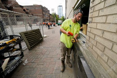 Michael Roberts replaces a window in a damaged building, in downtown Nashville, Tenn. Six months after a Christmas Day bombing ripped a hole in historic downtown, workers continue to chip away at cleanup efforts so that revitalization can begin. The tediously slow process has meant workers haven't been able to access some of the buildings until recent weeks