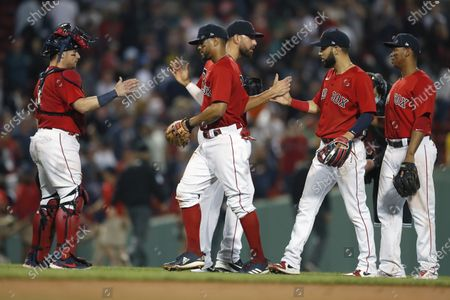 Boston Red Sox players, from left, Christian Vazquez, Xander Bogaerts, Matt Barnes, Marwin Gonzalez and Rafael Devers celebrate after defeating the New York Yankees during a baseball game, in Boston