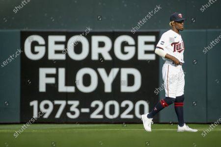 Minnesota Twins' Nick Gordon walks in front of a sign commemorating George Floyd before a baseball game with the Cleveland Indians, in Minneapolis. The Twins won 8-7