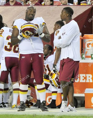 Washington Redskins defensive lineman Albert Haynesworth (92), left, shares some thoughts with Redskins wide receiver Malcolm Kelly (12), right, on the sidelines during the first quarter