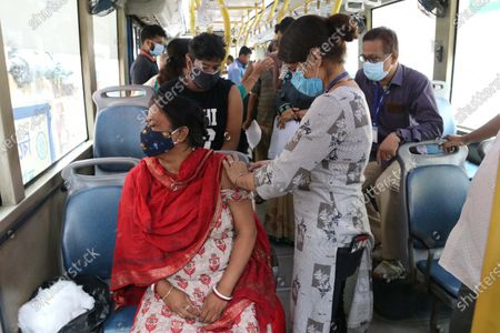 A health worker inoculates a sex worker  with a dose of the Covishield vaccine against the Covid-19 coronavirus at a vaccination on wheels in Kolkata On June 26,2021. Kolkata Municipal Corporation (KMC)  An air-conditioned bus was provided by the West Bengal goverment Transport Department for vaccinating priority groups at the different markets.