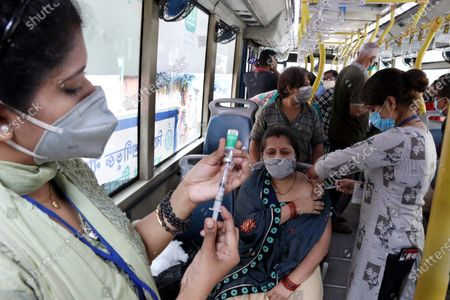 A health worker inoculates a women  with a dose of the Covishield vaccine against the Covid-19 coronavirus at a vaccination on wheels in Kolkata On June 26,2021. Kolkata Municipal Corporation (KMC)  An air-conditioned bus was provided by the West Bengal goverment Transport Department for vaccinating priority groups at the different markets.