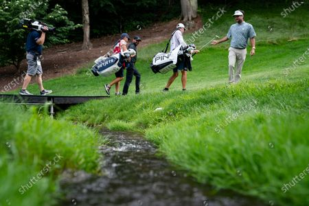 Bubba Watson, right, and his group-mate Jason Day cross a stream as they walk up to the 15th tee during the third round of the Travelers Championship golf tournament at TPC River Highlands, in Cromwell, Conn