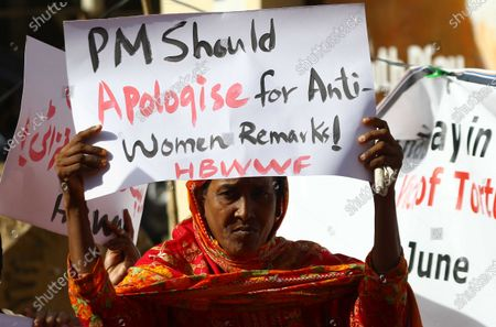 Pakistani women hold placards during a protest against the statement of the Prime Minister Imran Khan on women's clothing, in Karachi, Pakistan, 26 June 2021.In an interview on HBO, the Prime Minister had dubbed women's clothing as a cause of rape in Pakistan.