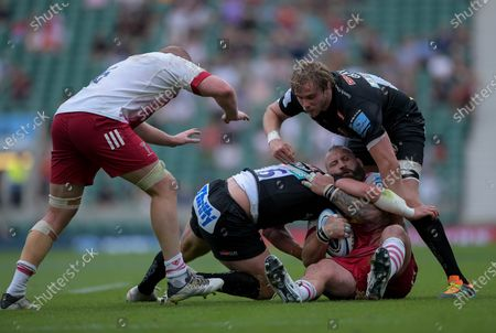 Joe Marler of Harlequins is tackled by Jannes Kirsten of Exeter Chiefs and Jonny Gray of Exeter Chiefs
