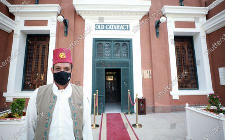 A bellman stands in front of the Old Cataract Hotel in Aswan, southern Egypt, 25 June 2021 (issued 26 June 2021).The Old Cataract was built in 1899 by Thomas Cook to house European travelers. Its guests included famous people as Winston Churchill, Howard Carter, Margaret Thatcher, Jimmy Carter, and Princess Diana.