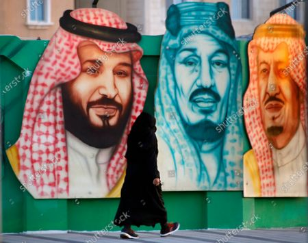 Stock Photo of Woman walks in front of a banner showing Saudi King Salman, right, his Crown Prince Mohammed bin Salman, left, and Saudi Arabia's founder late King Abdul Aziz Al Saud in Dammam, in the Kingdom's Eastern Province