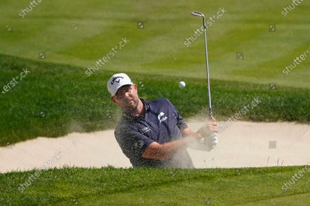 Marc Leishman, of Australia, hits out of a bunker on the 18th hole during the final round of the Travelers Championship golf tournament at TPC River Highlands, in Cromwell, Conn