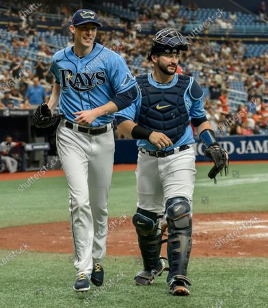 Stock Picture of Tampa Bay Rays starter Ryan Yarbrough, left, and catcher Mike Zunino head to the dugout after Los Angeles Angels' Taylor Ward was thrown out at the plate during the third inning of a baseball game, in St. Petersburg, Fla