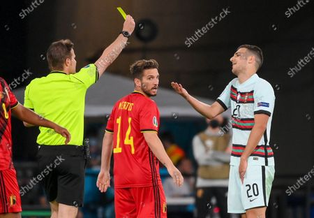 Portugal's Joao Cancelo, right, reacts to a yellow card from referee Felix Bryce during the Euro 2020 soccer championship round of 16 match between Belgium and Portugal at La Cartuja stadium, Seville, Spain