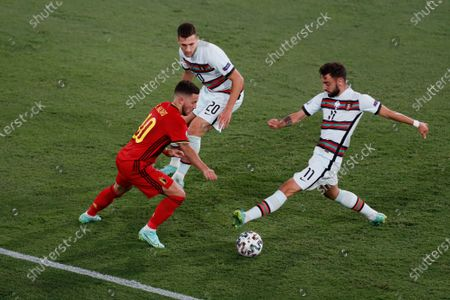Belgium's Eden Hazard, left, competes for the ball with Portugal's Joao Cancelo, center, and Portugal's Bruno Fernandes during the Euro 2020 soccer championship round of 16 match between Belgium and Portugal at La Cartuja stadium in Seville, Spain