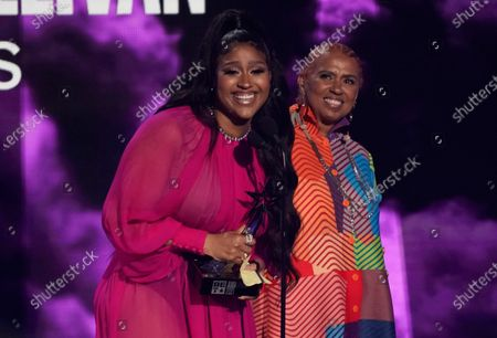 """Jazmine Sullivan accepts the album of the year award for """"Heaux Tales"""" as her mother Pam Sullivan looks on at right at the BET Awards, at the Microsoft Theater in Los Angeles"""