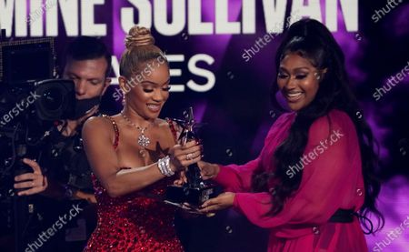 """Stock Picture of Saweetie, left, presents Jazmine Sullivan with the album of the year award for """"Heaux Tales"""" at the BET Awards, at the Microsoft Theater in Los Angeles"""