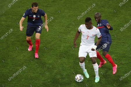 Breel Embolo of Switzerland is marked by Benjamin Pavard and Ngolo Kante of France