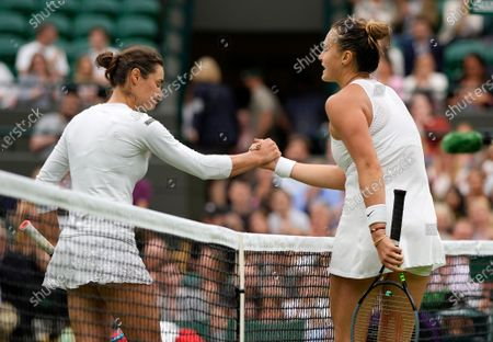 Belarus's Aryna Sabalenka, right, shakes hands with Romania's Monica Niculescu after winning the the first round women's singles match on day one of the Wimbledon Tennis Championships in London