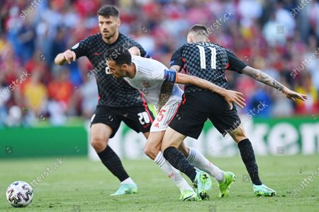 Spain's Sergio Busquets, centre, tries to get past Croatia's Bruno Petkovic, left and Marcelo Brozovic during the Euro 2020 soccer championship round of 16 match between Croatia and Spain at the Parken Stadium in Copenhagen