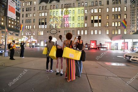 Stock Image of Marc Jacobs models stop and watch the Marc Jacobs show projection