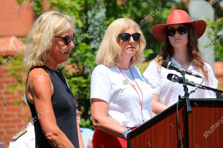 Andrea Chamblee, the widow of John McNamara who was one of the five people killed three years ago in the Capital Gazette mass shooting, speaks at the dedication of a memorial to the victims on in Annapolis, Md. Maria Hiaasen, the widow of slain newspaper editor Rob Hiaasen, is standing left. Summerleigh Winters, the daughter of Wendi Winters who also was killed in the attack, is standing right
