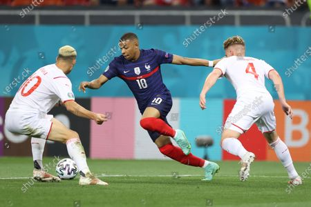 France's Kylian Mbappe, center, is challenged by Switzerland's Granit Xhaka, left, and Switzerland's Nico Elvedi during the Euro 2020 soccer championship round of 16 match between France and Switzerland at the National Arena stadium, in Bucharest, Romania