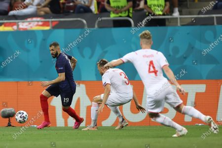 France's Karim Benzema, left, is challenged by Switzerland's Silvan Widmer, center, and Switzerland's Nico Elvedi during the Euro 2020 soccer championship round of 16 match between France and Switzerland at the National Arena stadium, in Bucharest, Romania