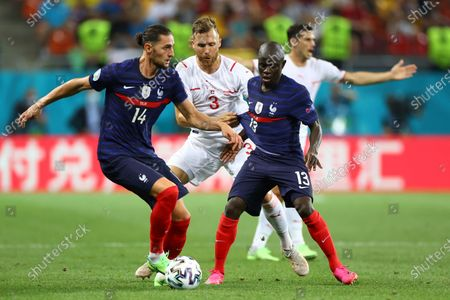 Switzerland's Silvan Widmer, center, is challenged by France's Adrien Rabiot, left, and France's N'Golo Kante during the Euro 2020 soccer championship round of 16 match between France and Switzerland at the National Arena stadium, in Bucharest, Romania
