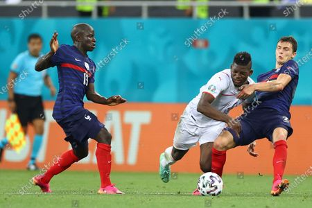Switzerland's Breel Embolo, center, fights for the ball with France's Benjamin Pavard, right, and France's N'Golo Kante during the Euro 2020 soccer championship round of 16 match between France and Switzerland at the National Arena stadium, in Bucharest, Romania